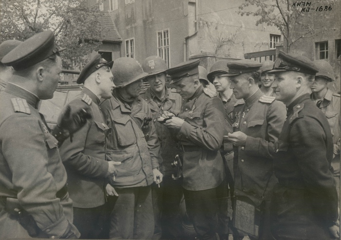 A man with a camera on one of the photos presented to the veterans by photo-reporter Ustinov. Shiver's smiley face is visible behind. Source: Yandex photo album by user kleck1127